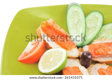 smoked salmon with tomatoes and lemon on green - stock photo