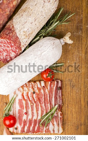 Smoked sausage with rosemary and peppercorns tomatoes and garlic close up - stock photo