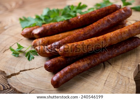 Smoked sausages over wooden background, close-up - stock photo