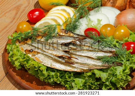Smoked sprat with salad, lemon, onions tomato, garnished with dill on a wooden kitchen board - stock photo