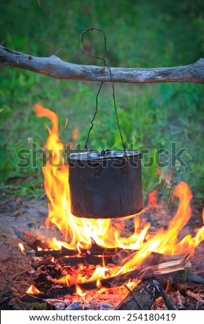 Smoked tourist kettle on fire in camp - stock photo