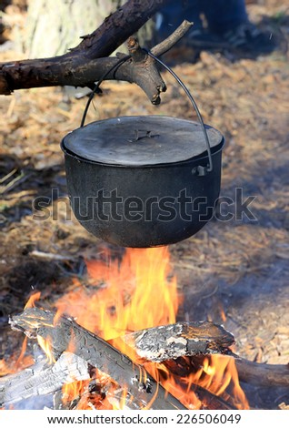 Smoked Tourist kettle on fire in forest camp - stock photo