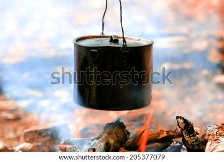 smoked tourist kettle over camp fire - stock photo