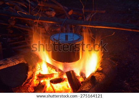 Smoked tourist kettle over camp fire in the evening - stock photo