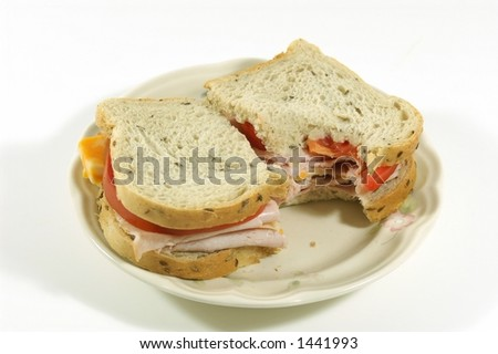 Smoked turkey, cheese and tomato sandwich on light rye bread against a white background. - stock photo