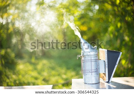 smoker for the beekeeper standing on a beehive - stock photo