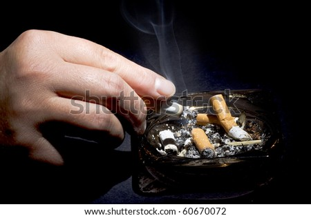Smoker hands and ashtray - stock photo