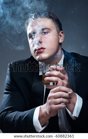 Smoker in suit with cigarette and glass of whiskey - stock photo