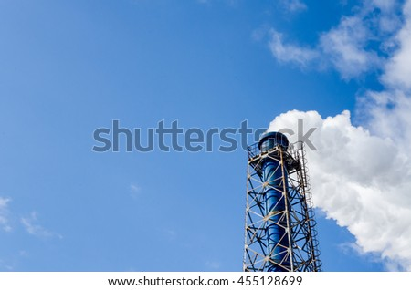 Smokestack and steam on blue sky background - stock photo