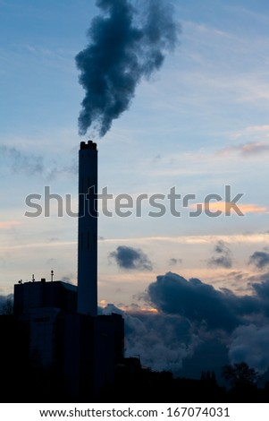Smokestack chimneys belching black smoke pollutants and carbon dioxide greenhouse gas into the atmosphere polluting and contributing to global warming - stock photo