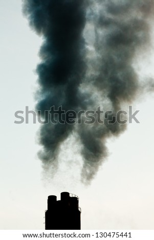 Smokestack chimneys belching black smoke  pollutants and greenhouse gas into the atmosphere polluting and contributing to global warming - stock photo