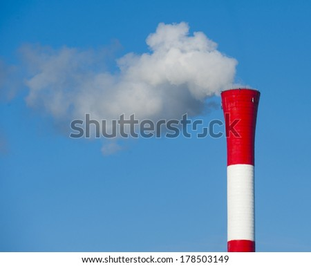 Smokestack pollution from coal power plant against clear blue sky - stock photo