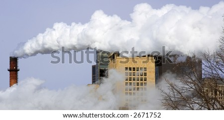 Smokestack sends out plume of smoke over city buildings - stock photo