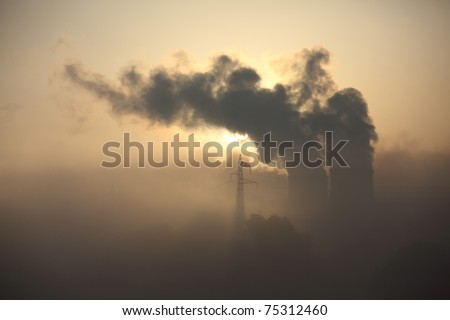 Smokestack with heavy pollution against a sunrise - stock photo