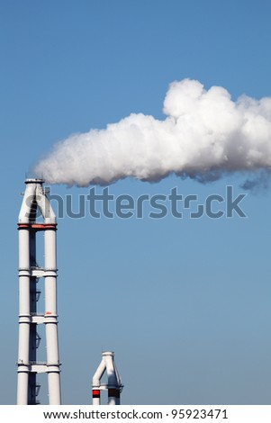 Smokestack with white smoke over blue sky - stock photo