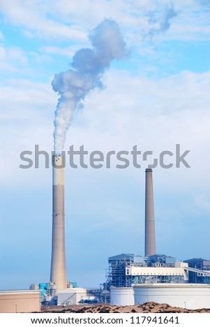 Smokestacks of power station on sky background - stock photo