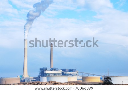 Smokestacks of power station on sky background - stock photo