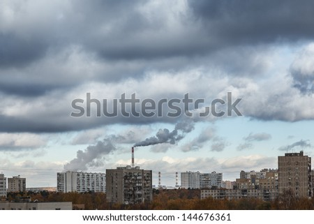 Smokestacks polluting cloudy sky with smoke over industrial city cityscape. - stock photo
