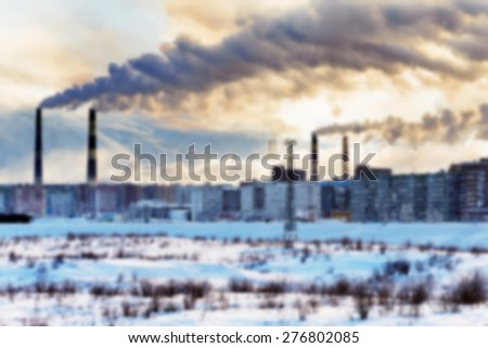 Smokestacks polluting the air over the city. Winter landscape. Abstract blur background. - stock photo