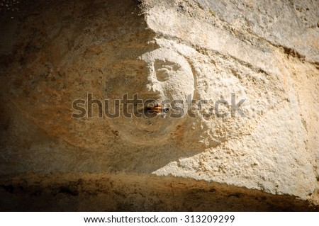 Smoking addiction. Stone human face (old building architectural detail) with real cigarette in the mouth. Vignette. - stock photo