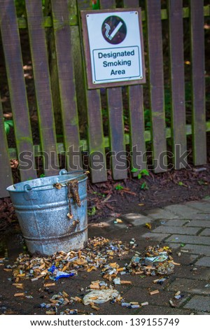 Smoking area grey bin with mess - stock photo