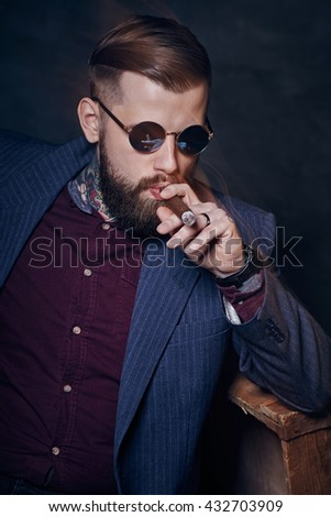 Smoking bearded male with tattooes on his arms.