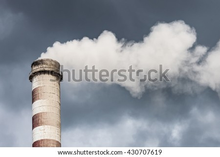 Smoking big industrial chimney in dark clouds. Concept for environmental protection