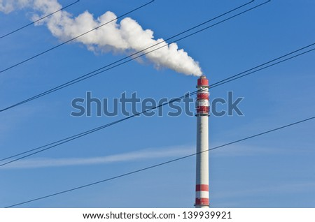 Smoking chimney beyond high voltage cables - heating plant - pollution in the air - stock photo