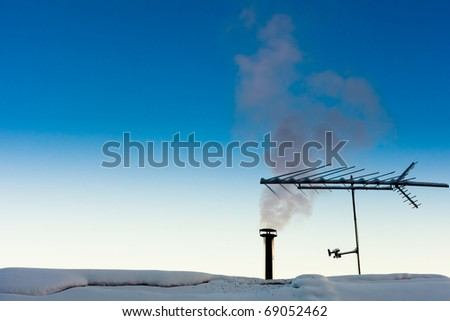 Smoking chimney of family home on a crispy cold clear winter day. - stock photo