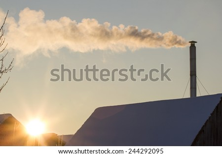 Smoking chimney on the cold winter morning. - stock photo