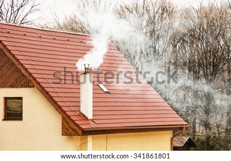 Smoking chimney on the red roof. Seasonal scene. Rural house. - stock photo