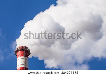 Smoking chimney pollution on blue sky - stock photo