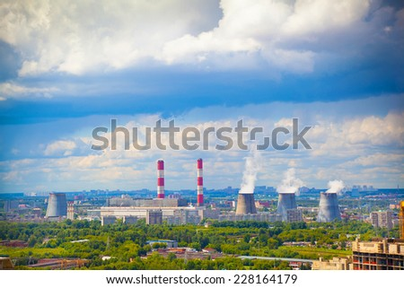 smoking chimneys from a power plant against a blue sky  - stock photo
