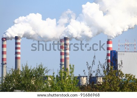 smoking chimneys from a power plant against a blue sky - Poland - stock photo