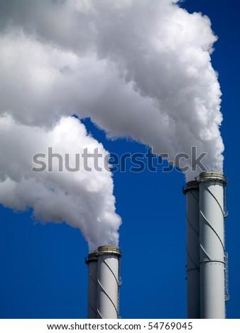 Smoking chimneys in industrial area - stock photo