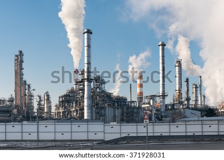 smoking chimneys of an oil refinery against blue sky - stock photo