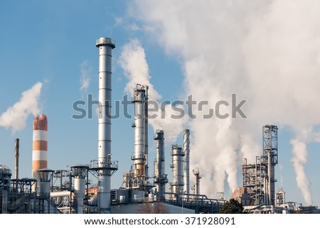 smoking chimneys of an oil refinery against blue sky