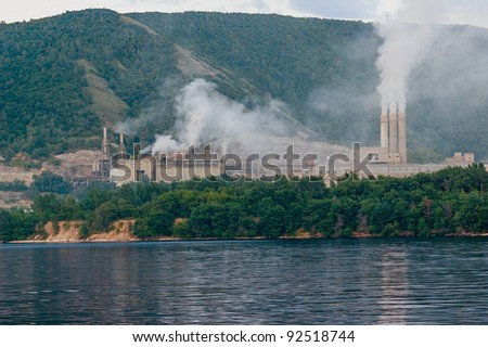 Smoking chimneys of the plant on the river - stock photo