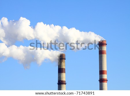 Smoking chimneys power against the blue sky