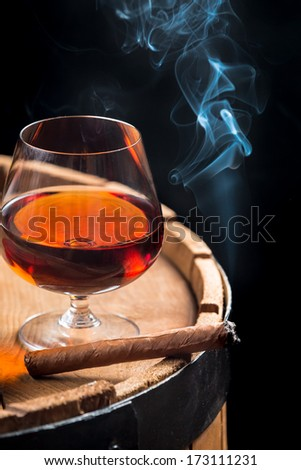 Smoking cigar and wooden brandy barrel - stock photo