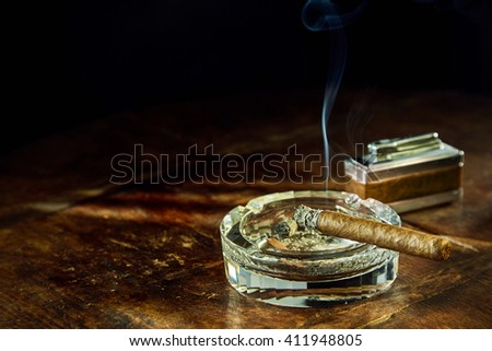 Smoking cigar sitting in round glass ashtray besides fancy lighter on wooden table - stock photo