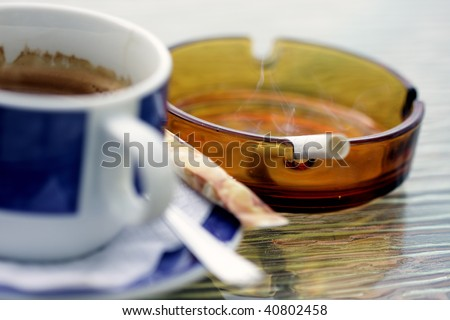 Smoking cigarette in ashtray and blue cup of coffee selective focus