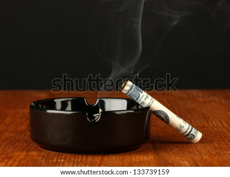 smoking cigarette of the 100 dollar bill and an ashtray on black background - stock photo