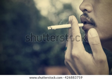 Smoking cigarette vintage effect tone. - stock photo