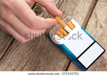 Smoking concept. Hand takes a cigarette out of pack.  - stock photo