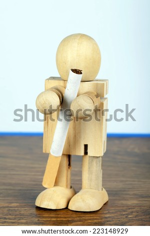 Smoking concept with wooden man holding a cigarette - stock photo