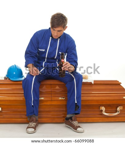 smoking, drinking beer man in blue overalls with hat sits on coffin