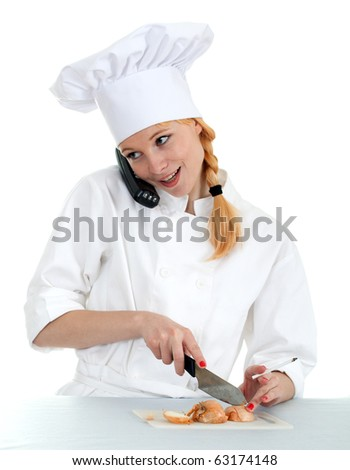 smoking female cook in white uniform cutting onion and speaking on the phone - stock photo