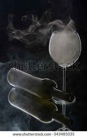 Smoking glass and lying bottle. Isolated on black background - stock photo