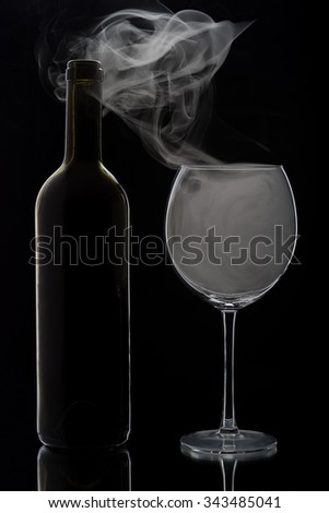 Smoking glass of red wine and the bottle. Isolated on black background - stock photo
